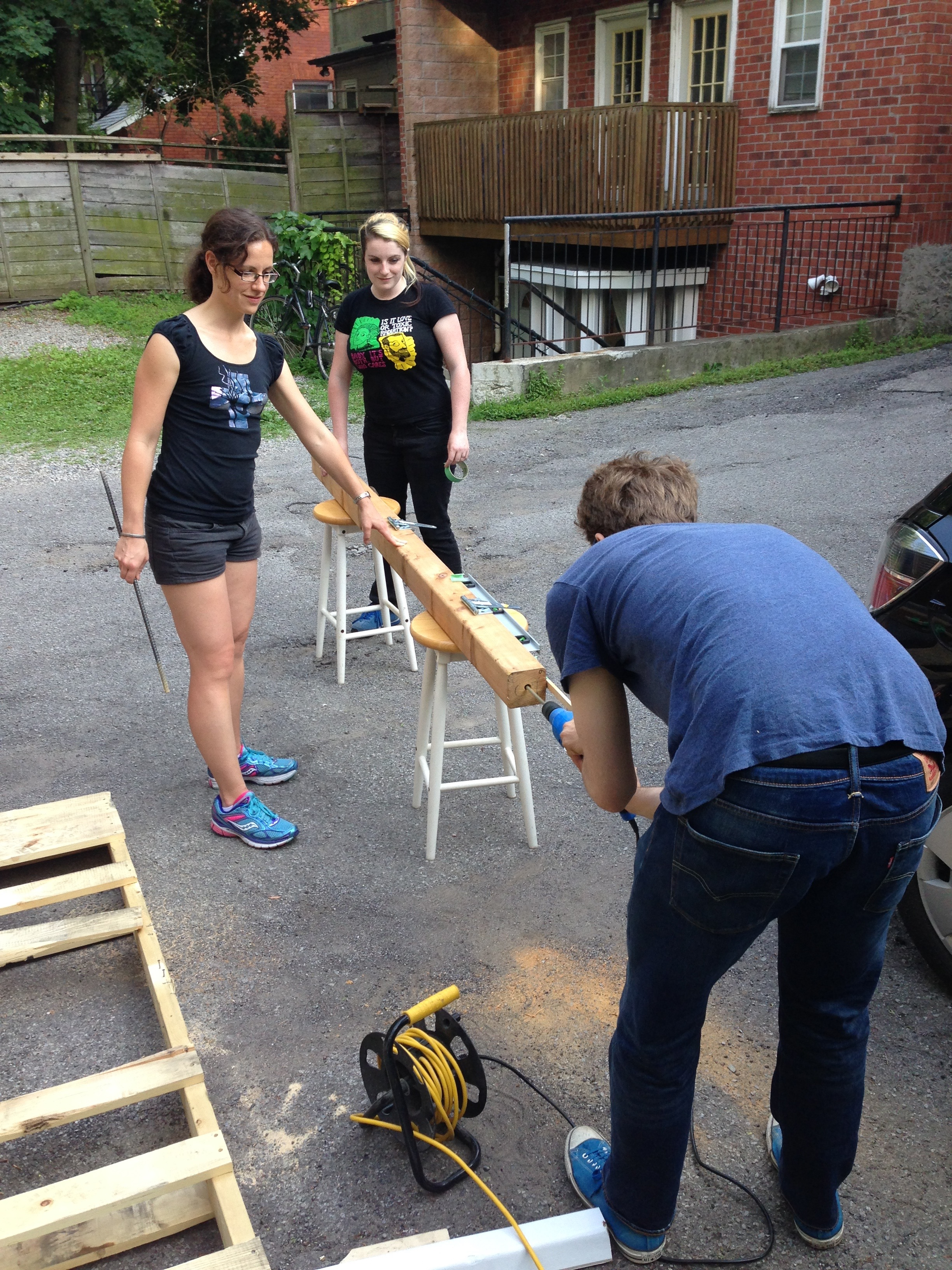 Mel and S help Geoff drill the base of a post 5.